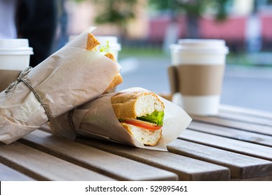 Chicken submarine sandwich from fresh baguette. Sandwiches with chicken, fresh vegetables and herbs on rustic wooden chopping board over wood backdrop, side view with coffee cup on background.