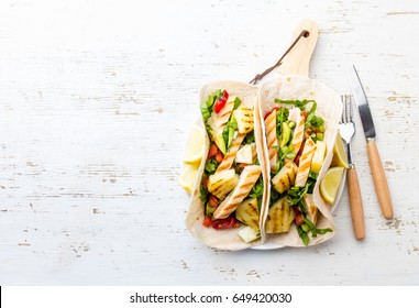 Chicken tacos with grilled pineapple and vegetables. Mexican fast food. Street tacos with barbecue chicken and pineapple on white background. Top view, copy space