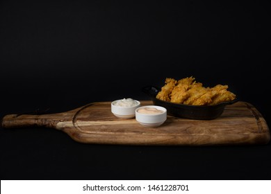 Chicken tenders on wood plate with black background