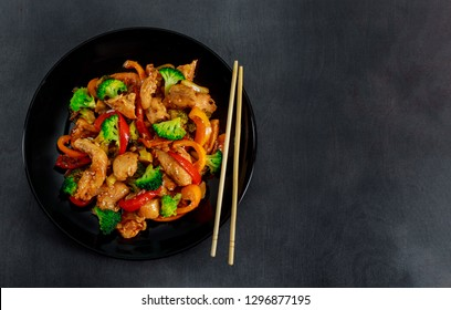 Chicken teriyaki with garnish of broccoli in dark bowls. chopsticks, wooden table, top view.