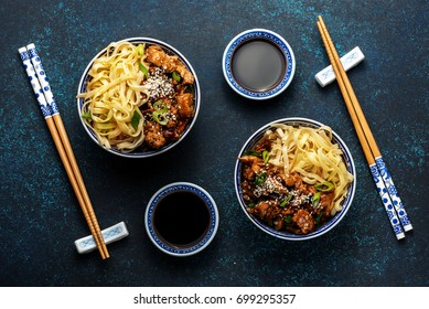 Chicken teriyaki on dark background with soy sauce and sesame seeds. Asian food. Noodles. Top view.