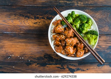 Chicken teriyaki, rice and broccoli in a white big bowl with chopsticks above. Wooden rustic table, top view.