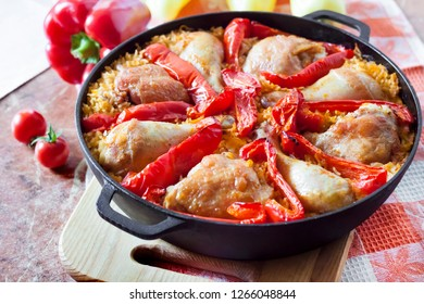 Chicken thighs and legs baked over a bed of rice and red bell pepper in cast iron stewpan