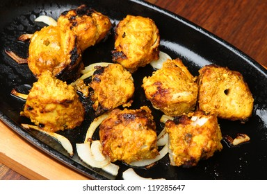 Chicken tikka in authentic cast-iron sizzler dish with onions.