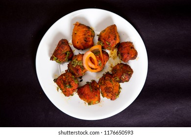 """Chicken Tikka"" - an Indian dish or cuisine prepared with barbecued chicken pieces  served as a starter or breakfast or brunch , also ideal filler in drinks party, clicked on a black background"
