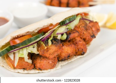 Chicken Tikka Kebab - Tandoori chicken tikka with salad in a pita bread. Served with chilli sauce, yoghurt and lemon wedges on a white background.