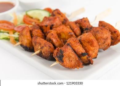 Chicken Tikka Kebab - Tandoori chicken tikka skewers served with salad, chili sauce and mint and yogurt raita on a white background.