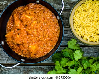 Chicken Tikka Masala Indian Takeaway Curry With Pillau Rice Against a Dark Wooden Background
