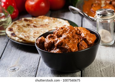 Chicken tikka masala served with bread naan in black dish