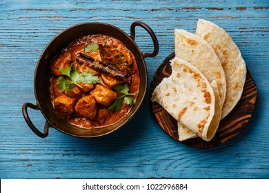 Chicken tikka masala spicy curry meat food and naan bread on blue wooden background