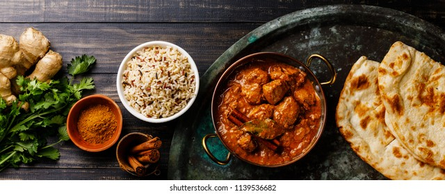 Chicken tikka masala spicy curry meat food Butter chicken with rice and naan bread on dark background
