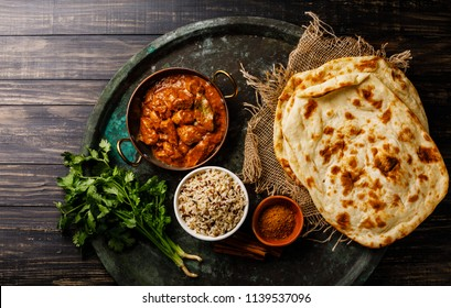 Chicken tikka masala spicy curry meat food with rice and naan bread on dark background