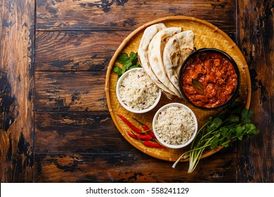 Chicken tikka masala spicy curry meat food Butter chicken in cast iron pot with rice and fresh naan bread on wooden background copy space