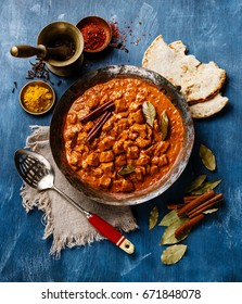 Chicken tikka masala spicy curry meat food in copper pan with naan bread on blue wooden background