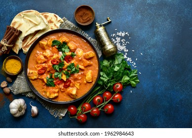 Chicken tikka masala - traditional dish of indian cuisine in a black bowl over dark blue slate, stone or concrete background.Top view with copy space.