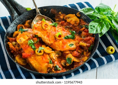 Chicken in tomato and olive sauce grnished in rustic frying pan