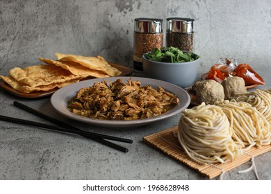 Chicken topping and raw yellow noodle displaying with meatball and green vegetable and fried dumplings