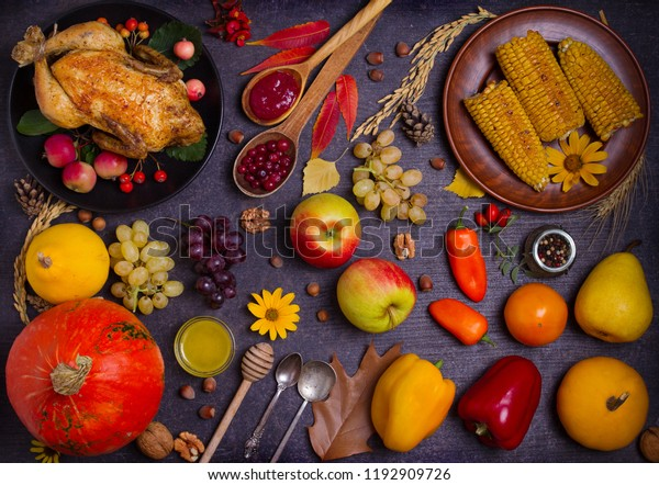 Chicken or turkey, autumn fruits and vegetables: corn, pumpkin, paprika, apples. Cranberry sauce, wheat. Thanksgiving food concept. Harvest or Thanksgiving background. View from above, top studio shot