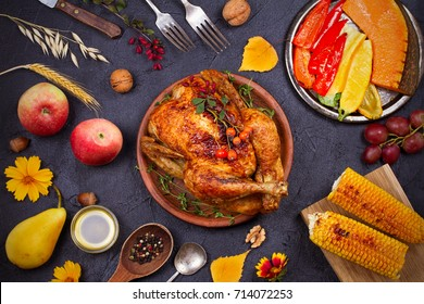 Chicken or turkey, fruits and grilled autumn vegetables: corn, pumpkin, paprika. Thanksgiving food concept. Harvest or Thanksgiving background. View from above, top studio shot, overhead, horizontal