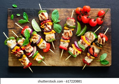 Chicken or turkey and vegetables cooked spicy skewers put on a board, ready to be served as summer party meal, view from above