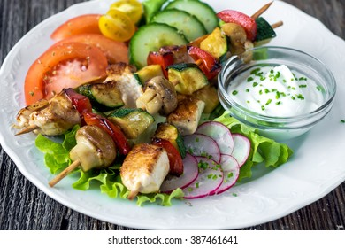 Chicken and vegetable skewers with  garlic dip and salad