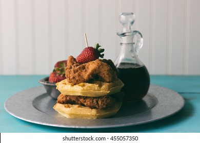 Chicken and waffles on a galvanized steel plate. Shown with syrup and strawberries.