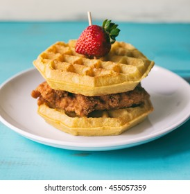 Chicken and waffles on a white plate shown with strawberry on top.