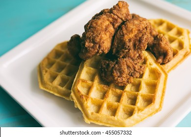 Chicken and waffles, shown on a white plate and turquoise table.