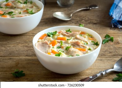 Chicken and Wild Rice Soup. Homemade fresh creamy soup with chicken, vegetables and wild rice in white bowl close up.