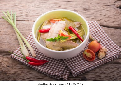 chicken wing tom yum in bowl on wood background.
