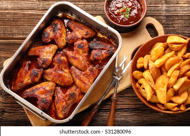 Chicken wings with baked potatoes and barbecue sauce on wooden background