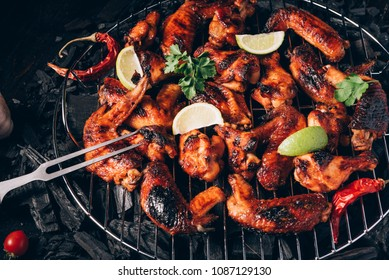 chicken wings of barbecue in honey sauce with lime slices. the dish is made and served in a rustic style