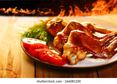 Chicken wings BBQ with vegetables on the plate, and fire on background