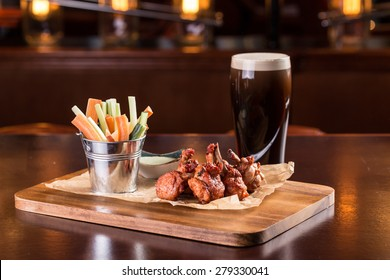 Chicken wings with blue cheese dip and glass of beer isolated on wooden table