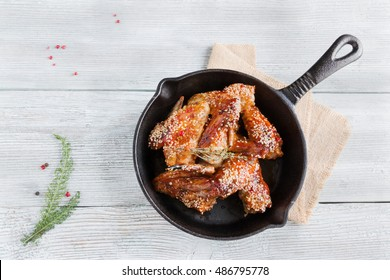 Chicken wings in cast-iron pan. Marinated in tomato and honey sauce. Baked with sesame seeds. Top view, wooden table.