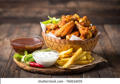 Chicken wings with dips on the wooden table