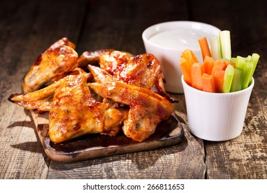 chicken wings with fresh vegetables and sauce on wooden table