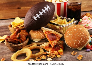 chicken wings, fries, and onion rings for football on a table. Great for Bowl football Game. and other unhealthy food with salt, fat and sugar