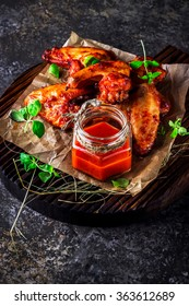 Chicken wings with hot tomato sauce on a chopping board. Grey stone background. Selective focus.