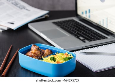 Chicken wings and noodles in bento box at office lunch