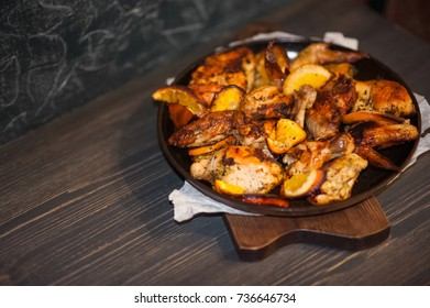 Chicken wings with oranges on a dark background. Place for text