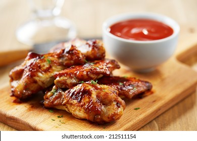 Chicken wings with sriracha sauce on wooden table