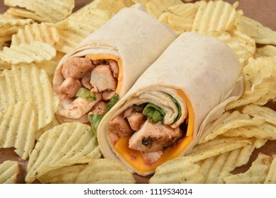 A chicken wrap sandwich with cheddar cheese on a mound of potato chips.  High angle view