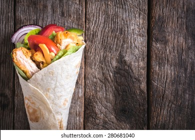 Chicken wrap sandwich on wooden background with blank space