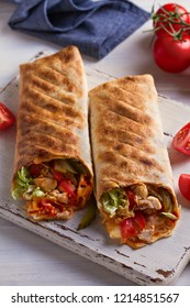 Chicken wraps with tomatoes, pickles, cabbage and onion on white chopping board and wooden table. Tortilla, burritos, sandwiches, twisted rolls