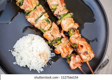 Chicken yakitori with white rice on a plate.