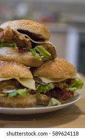 Chickenburgers with cheese, bacon and salad on a plate