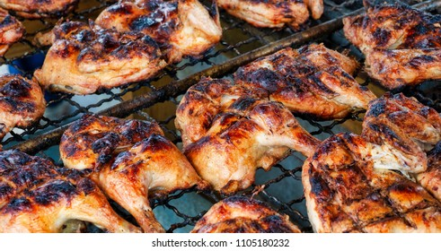 Chickens being barbecued on a grill over a charcoal fire.