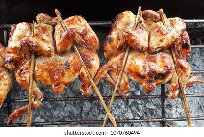 Chickens grilled on iron stove, fireplace, Thailand street food.