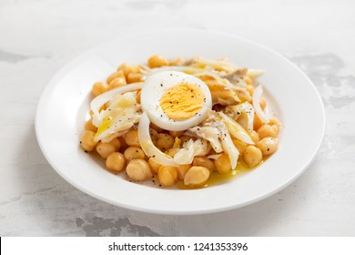 chick-pea with cod fish and boiled egg on white plate
